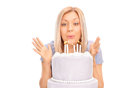 blow: Studio shot of an overjoyed blond woman blowing candles on a birthday cake isolated on white background
