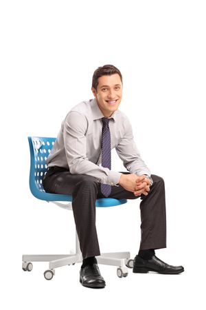 Vertical shot of a joyful businessman sitting on a blue chair and looking at the camera isolated on white background