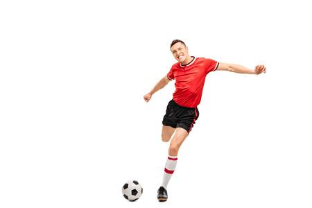 patada: Studio foto de una joven jugador de fútbol pateando una pelota y mirando a la cámara aislada en el fondo blanco