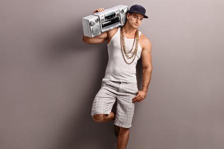 equipo de sonido: Hombre joven en ropa de hip-hop que lleva un ghetto blaster sobre su hombro y apoyado contra una pared gris Foto de archivo