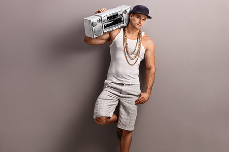 ghetto: Young man in hip-hop clothes carrying a ghetto blaster over his shoulder and leaning against a gray wall