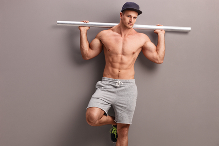 naked abs: Muscular shirtless man carrying a gray metal pipe on his shoulders and leaning against a gray wall