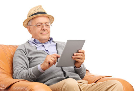 elderly people: Senior gentleman sitting in an armchair and working on a tablet isolated on white background Stock Photo