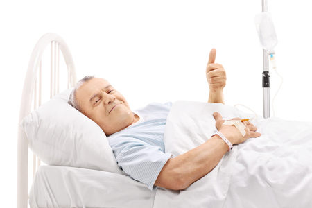 posing  agree: Cheerful senior patient lying in a hospital bed and giving a thumb up isolated on white background