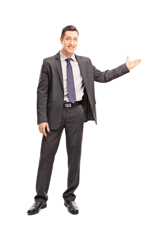 gray clothing: Full length portrait of a cheerful businessman gesturing with his hand and looking at the camera isolated on white background