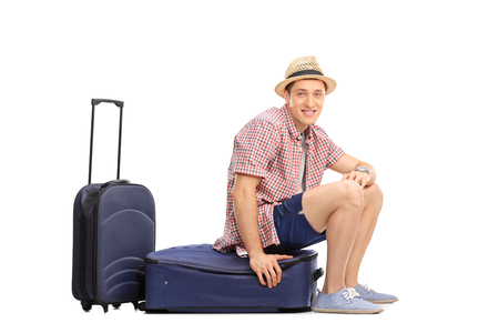 baggage: Cheerful male tourist sitting on his baggage and looking at the camera isolated on white background