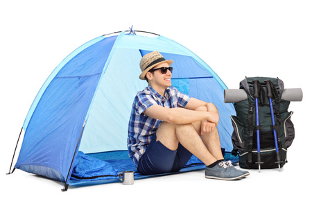 adventurer: Cheerful male hiker sitting on the floor in front of a blue tent with his backpack and hiking equipment beside him isolated on white background