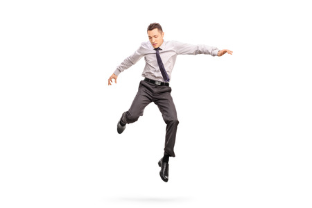 background person: Full length portrait of a young businessman jumping in the air and looking down isolated on white background