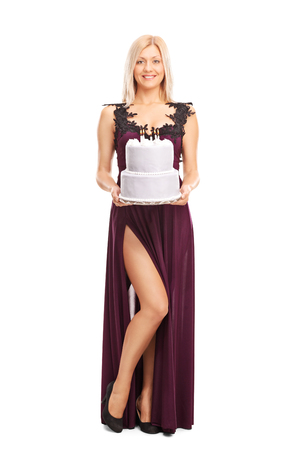 sexy birthday: Full length portrait of a young elegant woman carrying a birthday cake and looking at the camera isolated on white background Stock Photo