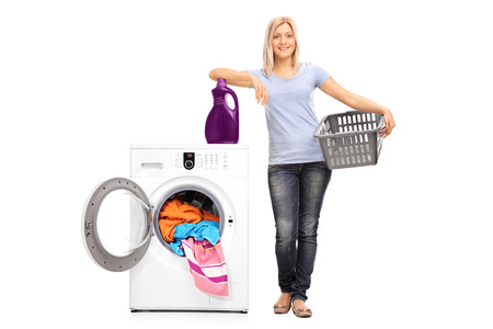 basket: Full length portrait of a young woman holding an empty basket and leaning on a laundry detergent on top of a washing machine isolated on white background Stock Photo