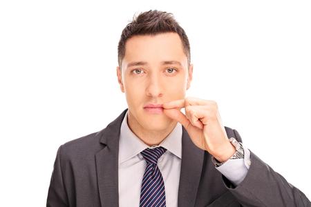 la boca: Primer plano de un joven empresario sosteniendo su mano en sus labios que simbolizan la boca cerrada aislada en el fondo blanco