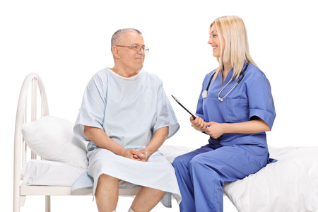 isolated man: Mature male patient and a young female doctor having a conversation seated on a hospital bed isolated on white background Stock Photo