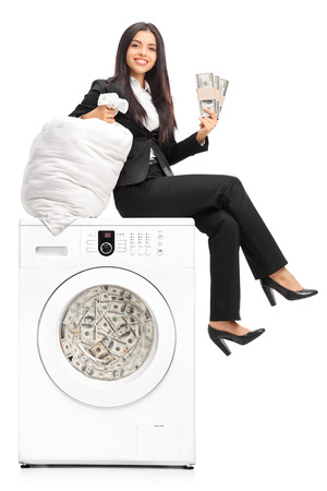 organized crime: Young businesswoman laundering money in a washing machine and looking at the camera isolated on white background