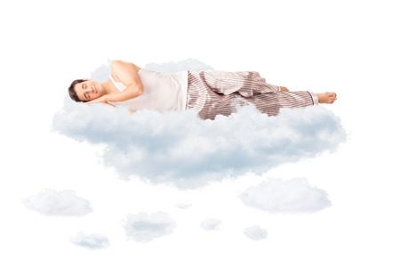 imagining: Young joyful man in pajamas sleeping on a cloud and dreaming isolated on white background