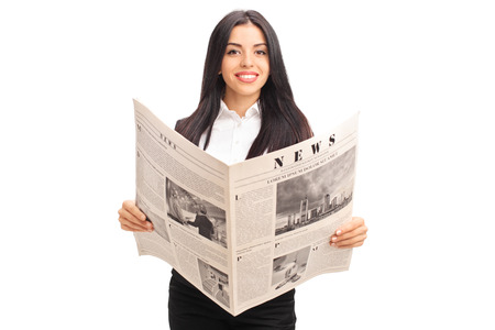 newspaper reading: Young cheerful businesswoman holding a newspaper and looking at the camera isolated on white background