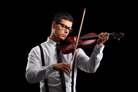 Jonge mannelijke violist die een akoestische viool op een zwarte achtergrond Stockfoto