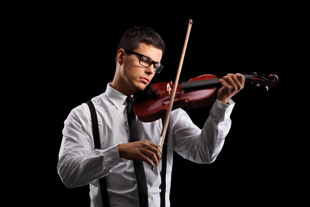 violins: Young male violinist playing an acoustic violin on a black background