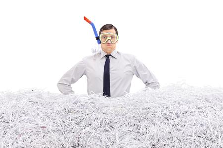白い背景に分離された細切りの紙の山に立っているダイビングのマスクと青年実業家