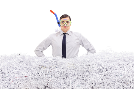 diving equipment: Young businessman with a diving mask standing in a pile of shredded paper isolated on white background