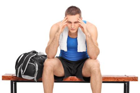 mirada triste: Atleta joven triste que se sienta en un banco de madera y mirando hacia abajo aislado en el fondo blanco Foto de archivo