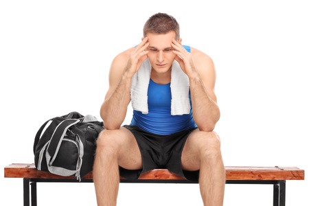 failure: Sad young athlete sitting on a wooden bench and looking down isolated on white background Stock Photo