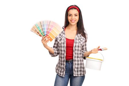 mujer sola: Mujer joven que sostiene un pincel y una muestra de color sobre fondo blanco