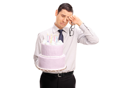 man sad: Sad young man holding a birthday cake and crying isolated on white background