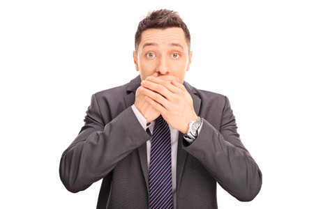 covering: Studio shot of a shocked young businessman covering his mouth and looking at the camera isolated on white background