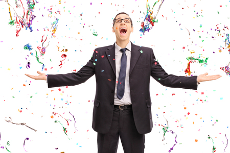 confetti: Studio shot of an overjoyed businessman standing in the middle of a lot of confetti streamers isolated on white background