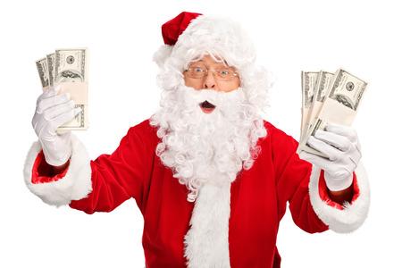 Kerstman die enkele stapels geld en kijken naar de camera op een witte achtergrond Stockfoto