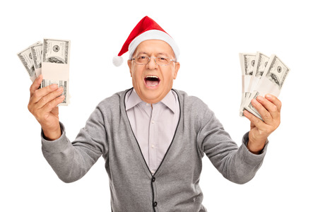 Ecstatic senior gentleman with Santa hat holding few stacks of money and looking at the camera isolated on white background