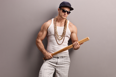 baseball sport: Muscular young man in hip-hop outfit holding a baseball bat and looking at the camera