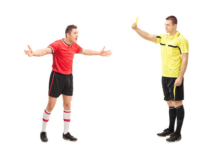 yellow card: Full length portrait of a football referee showing a yellow card to a displeased player isolated on white background