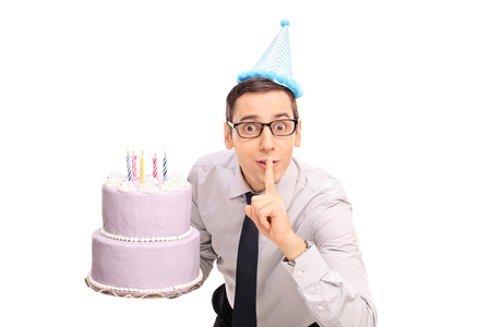 Joyful young man holding a birthday cake and a finger on his lips isolated on white background Stock Photo