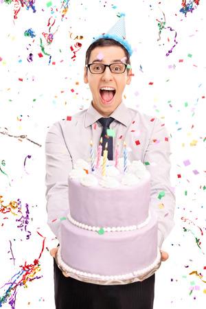 Tiro vertical de un hombre alegre joven que sostiene una torta de cumpleaños y mirando a la cámara con serpentinas confeti volando a su alrededor aisladas sobre fondo blanco Foto de archivo - 46949380