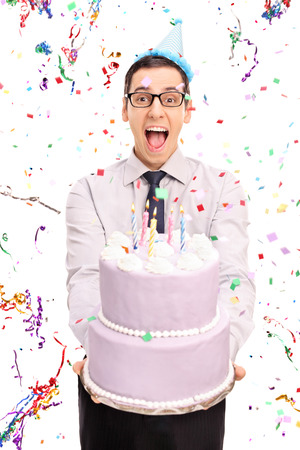background person: Vertical shot of a young joyful man holding a birthday cake and looking at the camera with confetti streamers flying around him isolated on white background Stock Photo