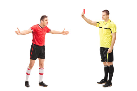 Full length portrait of a football referee showing a red card to an angry player isolated on white background Foto de archivo