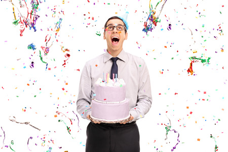 background person: Studio shot of a delighted man holding a birthday cake and looking at the confetti streamers flying around him isolated on white background