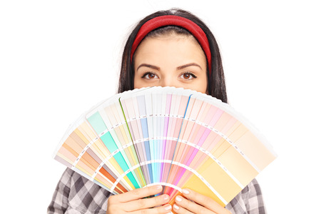 color swatch: Young woman hiding her face behind a color swatch and looking at the camera isolated on white background
