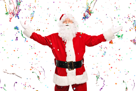happy holidays: Overjoyed Santa Claus standing in the middle of a bunch of flying confetti streamers isolated on white background