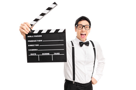 Excited young movie director holding a clapperboard and looking at the camera isolated on white background Stock Photo