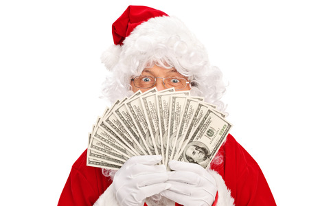 Santa Claus covering his face with a spread of money and looking at the camera isolated on white background Stock Photo