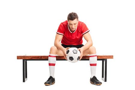 Jugador de fútbol joven triste que se sienta en un banco de madera y mirando hacia abajo aislado en el fondo blanco