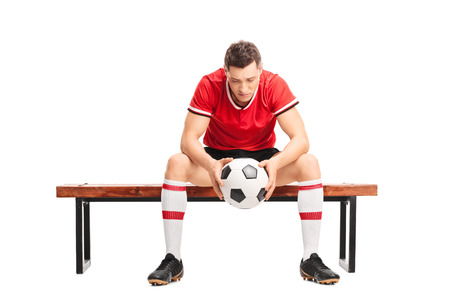 mirada triste: Jugador de fútbol joven triste que se sienta en un banco de madera y mirando hacia abajo aislado en el fondo blanco