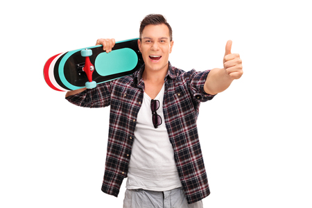 posing  agree: Excited man carrying a skateboard over his shoulder and giving a thumb up isolated on white background Stock Photo