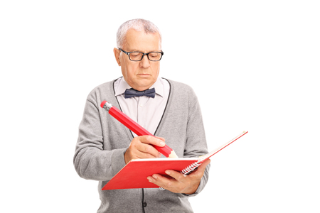 man writing: Studio shot of a mature teacher writing something in a notebook with a huge red pencil isolated on white background Stock Photo