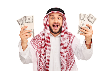 Excited young Arab holding few stacks of money and looking at the camera isolated on white background Reklamní fotografie