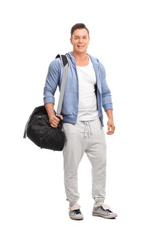 ropa deportiva: Retrato de cuerpo entero de un joven deportista que lleva una bolsa de deportes por encima del hombro y mirando a la cámara aislada en el fondo blanco