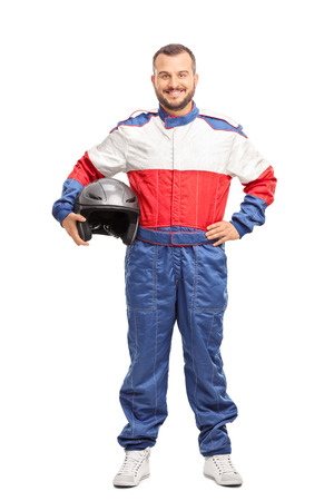 Full length portrait of a young male car racer in overalls holding a helmet and looking at the camera isolated on white background Standard-Bild