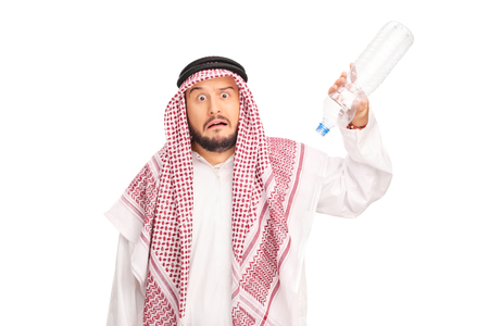 no water: Studio shot of a frightened Arab holding an empty plastic bottle with no water in it isolated on white background Stock Photo